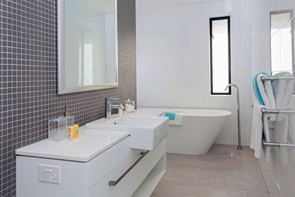 """MERIVALE, CHRISTCHURCH: A stand-alone bath is the feature of the smaller bathroom, which connects seamlessly to living areas on the lower level of the home. <a href=""""http://www.trademe.co.nz/property/residential-property-for-sale/auction-634412481.htm"""" target=""""_blank"""">Check it out.</a>"""