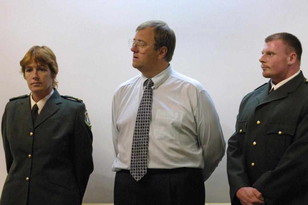 Mark Lundy was tried in 2001 for the murder of his wife and child a year earlier. Here he is pictured about to hear the verdict, flanked by officers of the court.