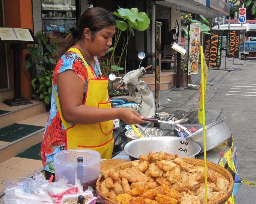 Local street vendor cooking springs rolls and more, so tasty and fresh. Street stall in Sukhumvit Soi 8, Bangkok, Thailand.