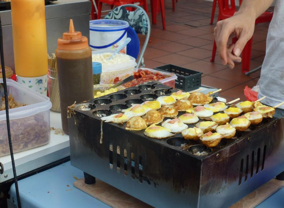 Skewered quail eggs with a little piece of sausage on top at the Melaka night markets in Malaysia pack a real protein punch. Question is - which came first? The cookware or the egg...