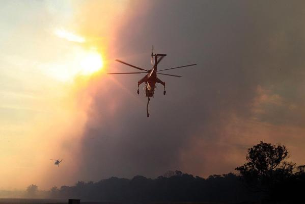 A helicopter water tanker takes off from Yanderra to fight nearby bushfires.