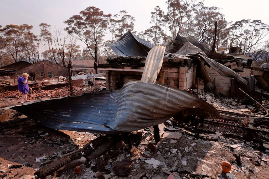 Local resident Delia Smith inspects her family's house after it was destroyed by a bushfire in the Blue Mountains suburb of Winmalee, located around 70 km west of Sydney.