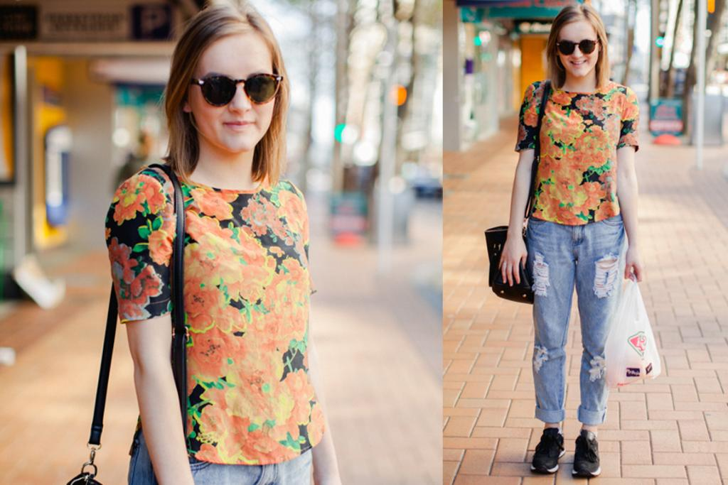 Louise, seen on Willis St in Wellington, wears a Liam floral top, Goldie boyfriend jeans, New Balance trainers and a Glassons handbag.