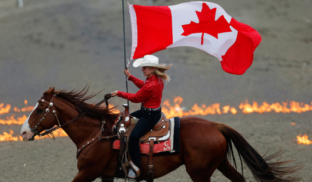 OH CANADA: A flag bearer rides with the Canadian flag before the start of the 101st Calgary Stampede rodeo in Calgary, Alberta.