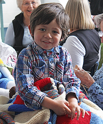CHUFFED: Kanye Griffiths, 3, is neighbours with Devonport knitting group member Lynn Dawson and chose his peggy square blanket.