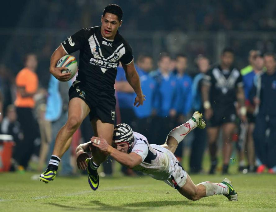 Kiwis wing Roger Tuivasa-Sheck attempts to skip out of a French tackle.