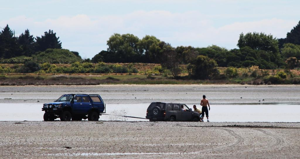 The Christchurch estuary's soft mud and a rising tide have claimed a 4WD despite frantic attempts to free the stricken vehicle.