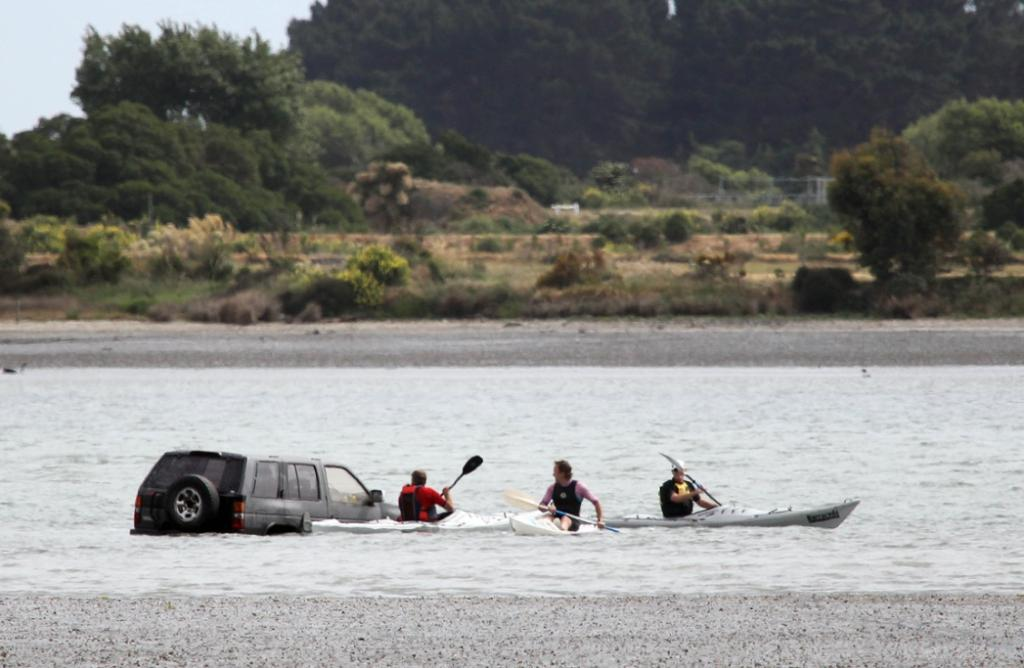 Kayakers on the estuary investigate the the stricken 4WD.