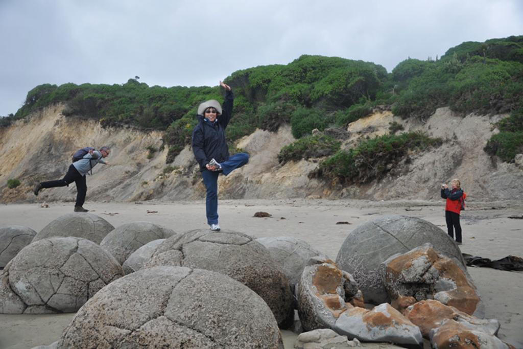 """Taken at Moeraki Boulders in Feb 2012. My mom decided to show my dad how to pose on the Boulder. A fellow traveller couldn't resist joining in on the """"competition""""."""