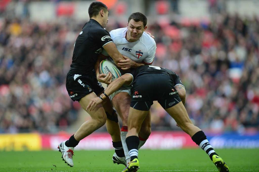 England's Brett Ferres is tackled by Shaun Johnson and another Kiwis defender.