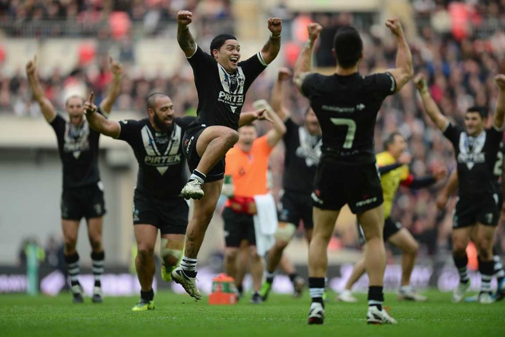 Issac Luke leaps in the air in celebration as Shaun Johnson (No 7) and other Kiwis players raise their arms after Johnson's match-winning conversion.