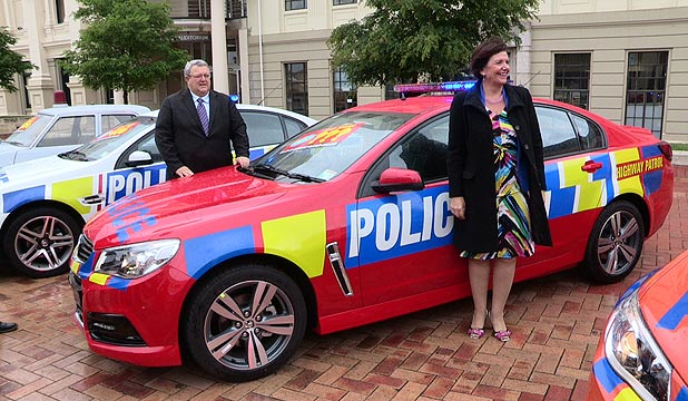 COP THAT: Transport Minister Gerry Brownlee (left) and Police Minister Anne Tolley check out one of the 28 new red patrol cars unveiled as part of a plan to make the vehicles more visible on New Zealand highways.