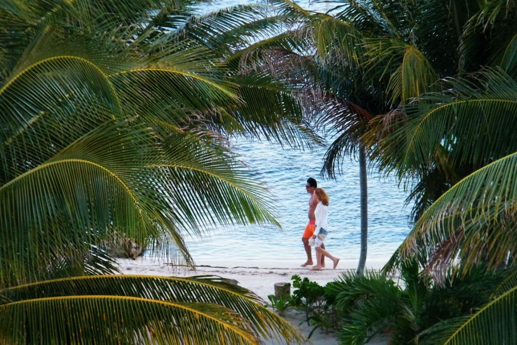 A couple enjoys the beach at the Blue Dolphin resort in Belize.