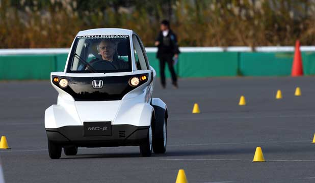 A journalist heads down the test track in Honda's MC-B electric car during a media event in Japan.