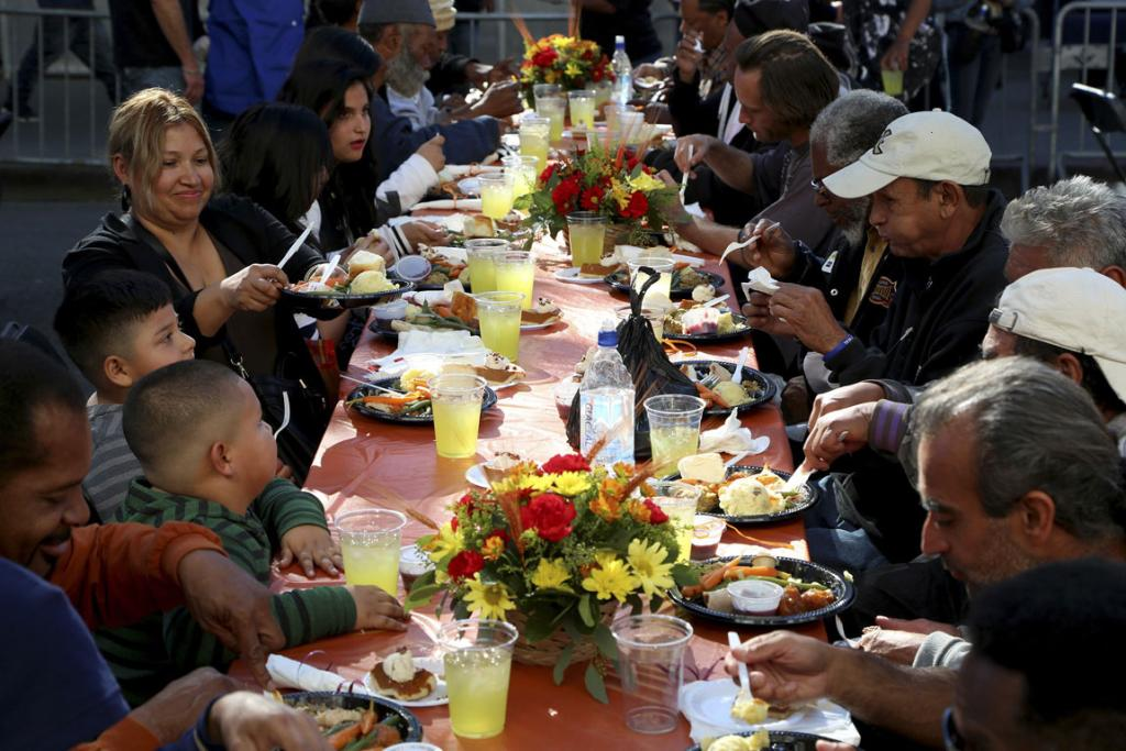 People sit down for an early Thanksgiving meal served to the homeless and others at Los Angeles Mission.