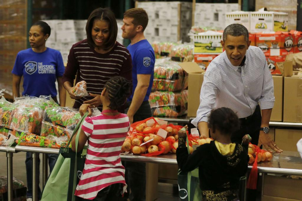 President Barack Obama and first lady Michelle Obama hand out Thanksgiving food at the Capital Area Food Bank in Washington.