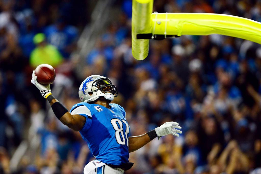 Detroit Lions wide receiver Calvin Johnson dunks the football over the goal post after scoring a touchdown during the third quarter of a NFL football game against the Green Bay Packers on Thanksgiving at Ford Field.