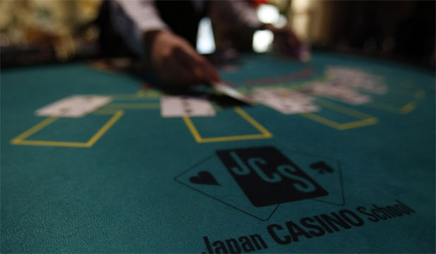 HOT SPRINGS ARE PASSE: A logo of Japan casino school is seen as a dealer puts cards on a mock black jack casino table during a photo opportunity at an international tourism promotion symposium in Tokyo.