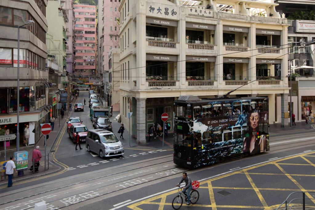 A man rides a bicycle next to a tram passing by a Chinese pawn shop that has been restored and partially converted into a restaurant at Hong Kong's Wanchai district.