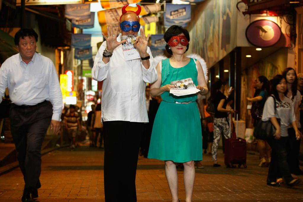 A passerby looks on as Allan Zeman (C), pioneer of Lan Kwai Fong, and former Secretary of Security and lawmaker Regina Ip (R) pose as an angel and a devil at Lan Kwai Fong in Hong Kong