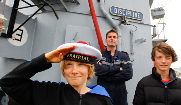 PRARIAL: Cousins Tristan Harris, left and Joseph Bahr both 12, have a look around under the watchful eye of navigator Ivan Gentil. The discipline sign is one of the navy mottos on the ship.