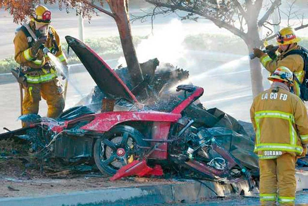 Firefighters extinguish the fire in the car where actor Paul Walker and his friend Roger Rodas were killed.