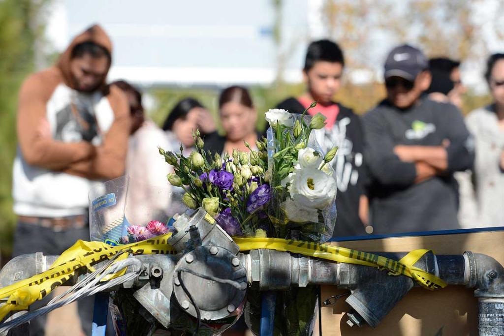 Fans gather and place flowers at the scene of a fiery crash that killed Fast and Furious actor Paul Walker.