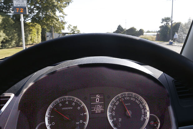 The speedometer on a 2012 Suzuki Swift shows 80kmh while a roadside speed display in Main Road Hope shows 72kmh.