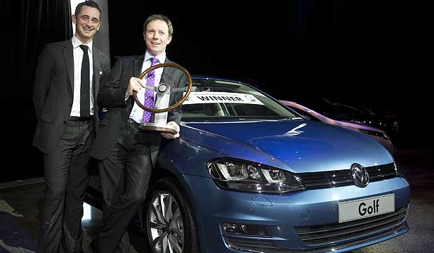 Volkswagen NZ marketing manager Michael Cope, left, and Scott Kelsey, Volkswagen NZ sales and operations manager stand in front of a VW Golf with the NZ Motoring Writers' Guild's car of the year award.
