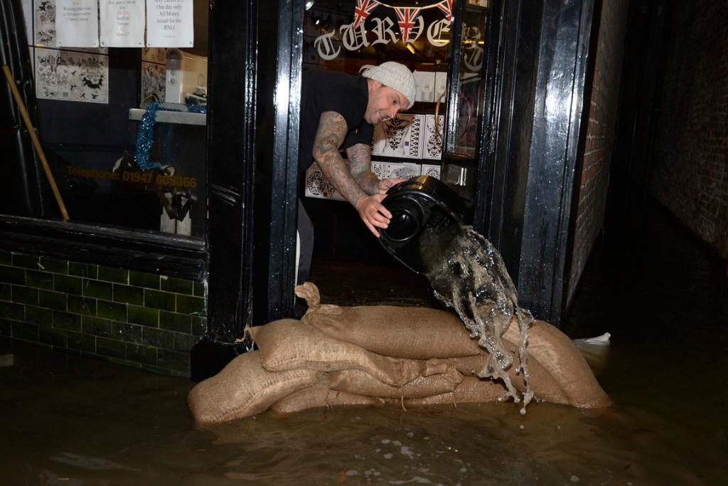 Shop owner Kevin Close bails floodwater from his tattoo shop in Whitby, northern England .
