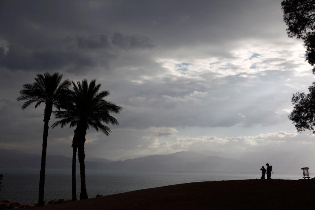 Israeli travellers are silhouetted as they walk near the shore of the Dead Sea.