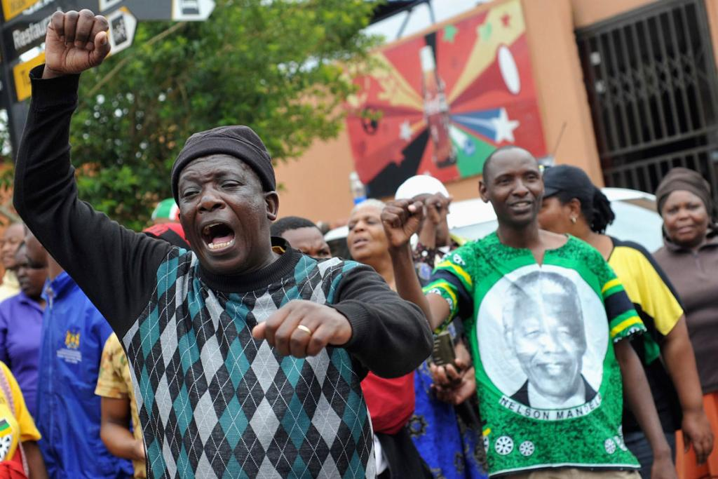 STREET SYMPATHY: Mourners react with song and dance on the street in Soweto where Mandela once lived.