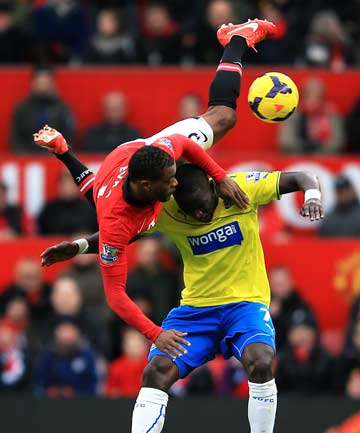 HEAD OVER HEELS: Manchester United's Patrice Evra tumbles over Newcastle United's Moussa Sissoko during their Premier League match at Old Trafford. Newcastle won 1-0.