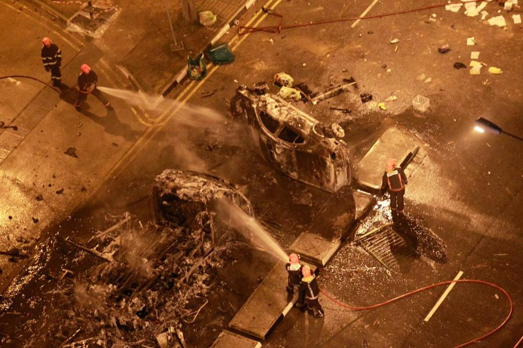 Singapore's civil defence officers extinguish burning vehicles following a riot in Singapore's Little India district.