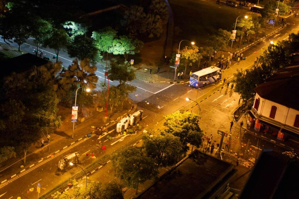 A view from a high-rise flat shows two overturned police cars (centre) and several other damaged vehicles along Race Course Road following a riot near Singapore's Little India district. Local media said a mob of about 400 set fire to an ambulance and police cars during the riot.