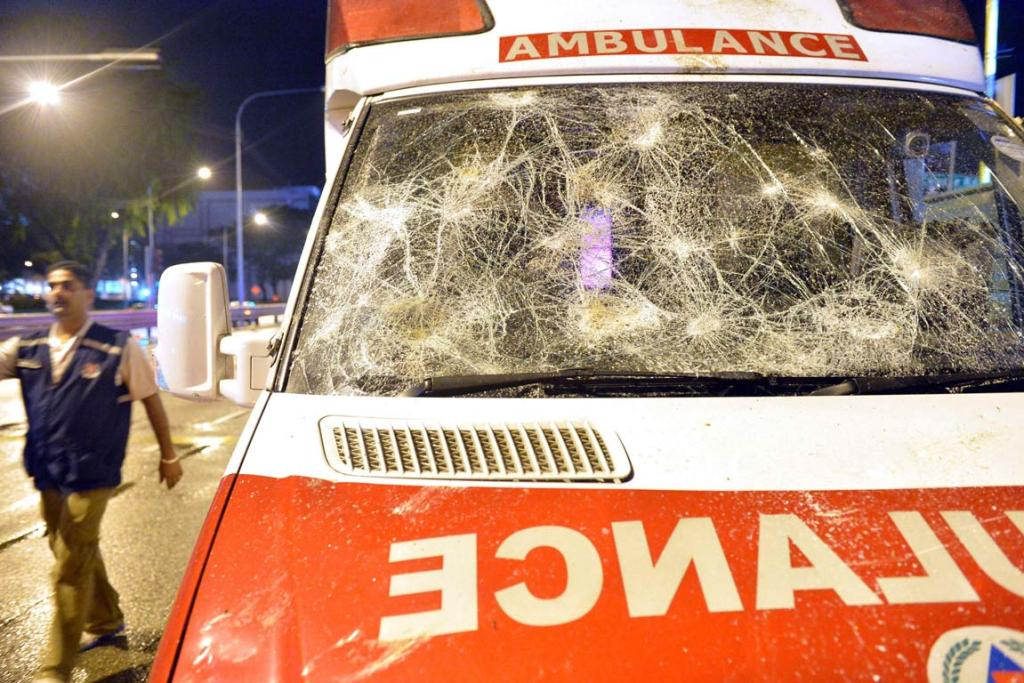 A man walks past an ambulance damaged in a riot in Singapore's Little India district.