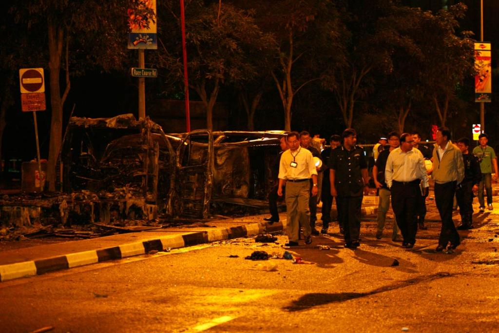 Singapore's Deputy Prime Minister Teo Chee Hean (front right) and Minister in Prime Minister's Office S Iswaran (front, second right) look at the site of two burnt vehicles following a riot in Singapore's Little India district.