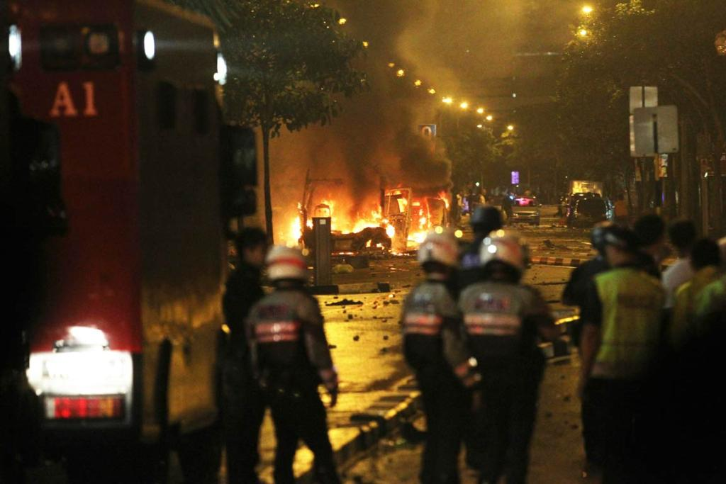 Riot policemen watch burning vehicles during a riot in Singapore's Little India district.