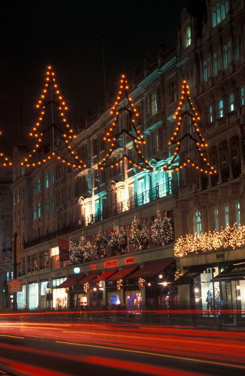 Shopfronts are illuminated with festive Christmas lights in London's vibrant West End shopping district.