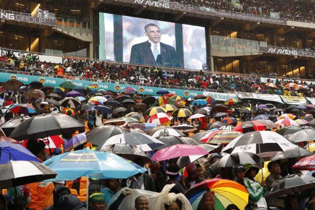 Mourners cover up with umbrellas as US President Barack Obama delivers his eulogy.