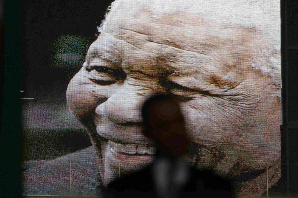 An image of Nelson Mandela shows on the big screen as US President Barack Obama speaks.