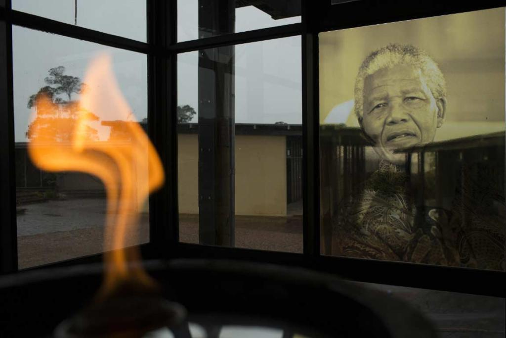 A flame burns near a portrait of Nelson Mandela at the Nelson Mandela Museum in Qunu.