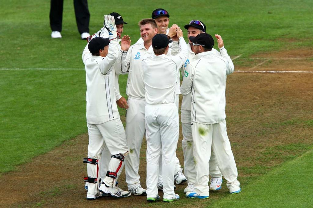 Corey Anderson (centre) is congratulated by team-mates after sending Kirk Edwards back to the pavillion.