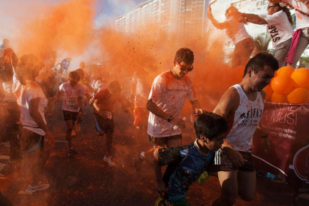 """Organizers throw colored powder at runners during a """"Cancun at Color"""" race in the tourist destination of Cancun."""