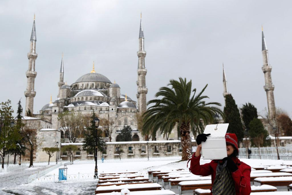 A foreign tourist, with the Ottoman-era Sultanahmet mosque, known as the Blue mosque in the background, takes souvenir photos as she strolls in snow-covered Sultanahmet square in Istanbul.