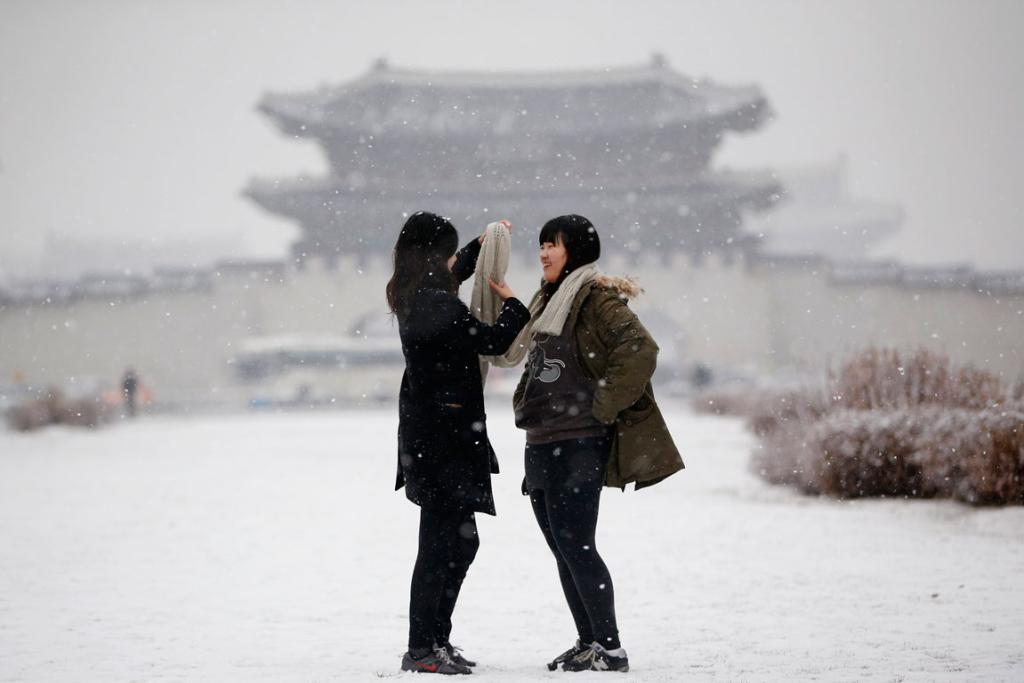 A woman helps her friend to adjust her scarf during snowfall in winter, as Gyeongbok Palace is pictured in the background, in central Seoul.