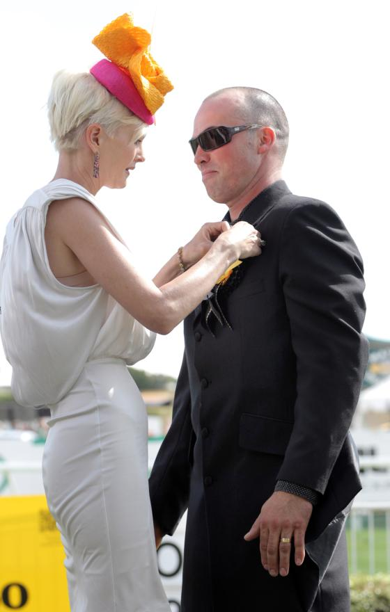 New Zealand Thoroughbred Racing ambassador Kylie Bax presents a prize to the winner of the Diamond Jewellers Best Dressed Man competition, Richard Fulton.