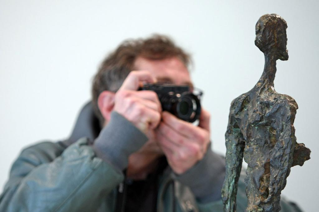 A visitor photographs the sculpture 'Woman of Venice IV' by Alberto Giacometti in the Kommandantenhaus, the newly-added building to the Berggruen Museum.
