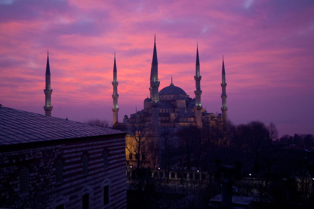 The sun rises behind the Blue Mosque in the Sultanahmet area of Istanbul.