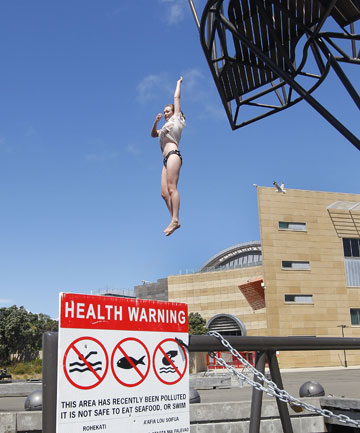 MURKY DEPTHS: Meghan Coomber leaps off the Taranaki St Wharf diving platform despite health warnings. It has been closed since February and is not expected to reopen until next February.